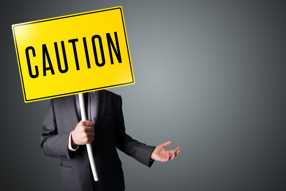 Businessman standing and holding a yellow caution sign in front of his head.jpeg